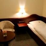 Das Einzelbett im kleinen Separee mit Sessel und Tisch